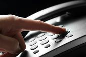 foto of telephone operator  - Finger pressing number button on telephone to make a call - JPG