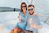 stock photo of yachts  - Cheerful young couple holding glasses with champagne and looking at camera while sitting on the board of yacht - JPG