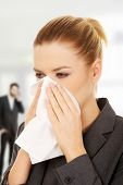 picture of sneezing  - Businesswoman with an allergy sneezing into tissue - JPG