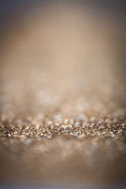 foto of glitter  - Holiday abstract glitter background with blinking lights and gold defocused texture - JPG