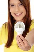 Happy young woman holding led bulb