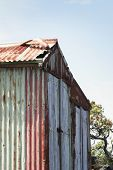 stock photo of scoria  - a weathered boat shed sits on the rocky shore of rangitoto island hauraki gulf new zealand