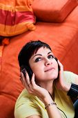 Young woman is listening music on a headphone in the livingroom. poster