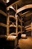 image of wine cellar  - Winebottles stacked in the old cellar of the winery - JPG