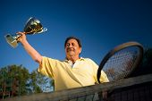 pic of older men  - Active senior man in his 70s is posing on the tennis court with cups in hands - JPG