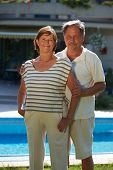 Portrait of happy active senior couple posing outdoor in front of home.