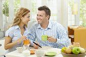 Постер, плакат: Счастливая пара пить кофе у себя дома сидя на стол завтрак глядя друг на друга улыбаясь