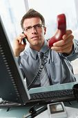Businessman with glasses busy talking on mobile phone handing over landline call to answer in office