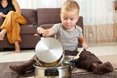 Little boy sitting on carpet in kitchen playing with cooking pots, mother sitting on sofa in backgro