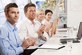 stock photo of training room  - Happy business people sitting at table in meeting room clapping listening to presentation - JPG