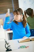 Elementary age school girl looking at test tube in science class at primary school.