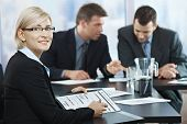 Smiling businesswoman holding documents sitting in meeting room with coworkers.