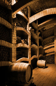 picture of wine cellar  - Winebottles stacked in the old cellar of the winery - JPG