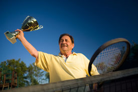 image of older men  - Active senior man in his 70s is posing on the tennis court with cups in hands - JPG