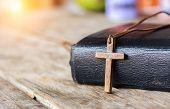 Closeup Brown Christian Cross Necklace Next To Holy Bible poster