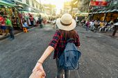 Back Side Of Young Asian Traveling Women Leading By Holding Her Boyfriend Hand In Khaosan Road Walki poster