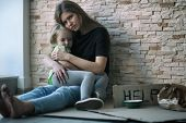 Homeless poor woman and her little daughter sitting near brick wall and asking for help poster