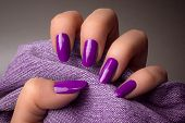 The Female Hand With Purple Nails Is Holding Purple Denim Textile On Gray Background. Manicure Conce poster