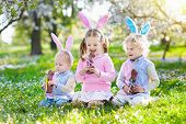 Garden Easter Egg Hunt. Kids Eat Bunny Chocolate. poster