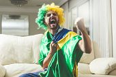 Brazilian fan watching a soccer match at home poster