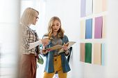Fashionable Magazine Editors Working With Documents At Color Palette On Wall poster