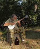 foto of hillbilly  - an old hillbilly banjo player with his moonshine jug playing an appalachian folk song - JPG