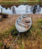 An Old Boat Lies On The Shore. The Boat Is Tied With A Chain To A Piece Of Rusty Pipe. On The Ground poster