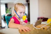 Little Girl With Allergic Asthma Using Inhaler And Watching Cartoons On A Smartphone. Girl Inhales M poster