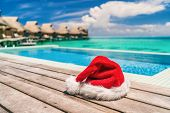 Christmas Santa Claus luxury vacation gift hotel holidays - hat by the infinity swim pool of high en poster