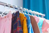 Pastel Color Childrens Clothes In A Row On Open Hanger Indoors. Clothes For Little Ladies Hung In T poster