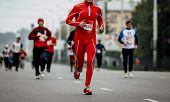 Male Runner In Red Tracksuit Run Marathon Ahead Of Group Runners poster
