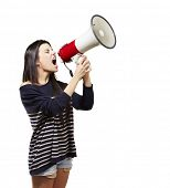 stock photo of public speaking  - young woman shouting with a megaphone against a white background - JPG