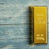Ingot Of Pure Gold Metal Bullion On A Background Of Blue Wooden Boards. poster