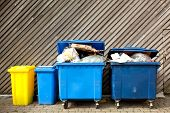 stock photo of waste management  - overfilled trash of large wheelie bins for rubbish - JPG