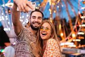 Image of a pleased positive loving couple walking outdoors in amusement park take a selfie mobile ph poster