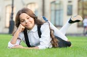 School Fashionista. Little Child In School Fashion Relax On Green Grass. Small Vogue Model With Cute poster