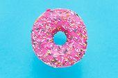 Sprinkled Pink Donut. Glazed Sprinkled Donut On Blue Background. Top View, Copy Space poster