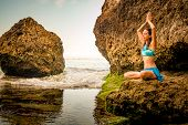 Yoga Lifestyle. Young Woman Meditating, Practicing Yoga And Pranayama At The Beach. Hand Raising In  poster