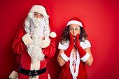 Middle age couple wearing Santa costume and glasses over isolated red background afraid and shocked, poster