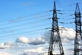 Towers Of Electric Main With The Wires Against The Blue Sky With Clouds. High Voltage Lines And Powe poster