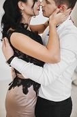 Beautiful Couple In Love Hugging And Kissing In The Interior. Sexy Brunette Model Girl In Skirt And  poster