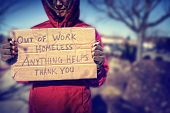picture of unemployed people  - a homeless person with a sign - JPG