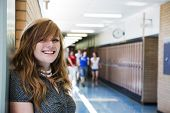 picture of nose piercing  - A happy high school student with other students running in the school hallway - JPG