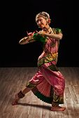stock photo of krishna  - Young beautiful woman dancer exponent of Indian classical dance Bharatanatyam in Krishna pose - JPG