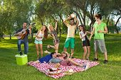 picture of jive  - Lively group of friends in the park singing and dancing along to guitar music played by one of the boys as they enjoy a picnic outdoors - JPG