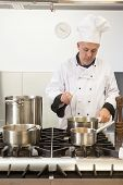 Focused head chef looking into pot in professional kitchen
