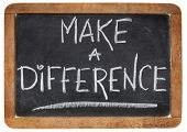 make a difference -motivational phrase - white chalk handwriting on a vintage slate blackboard