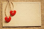 stock photo of two hearts  - Two red plastic hearts and carton card on a canvas background - JPG
