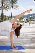 stock photo of kundalini  - Middle aged senior woman doing yoga pose in front of pool - JPG