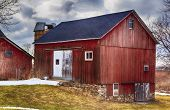 image of red siding  - Large red bank barn. New Roof. Crisp colors and overcast sky.